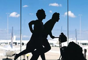 Two people running through an airport.