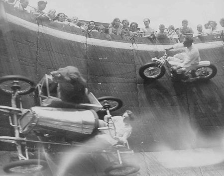 Wall of death with a woman driving a car, with lion in passenger seat, while motorcycle rides on the wall above them. No, seriously.