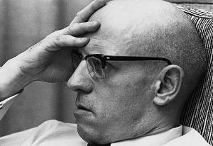 A picture of Michel Foucault, mostly head shot, with his hand on his forehead, wearing glasses, apparently deep in contemplation.