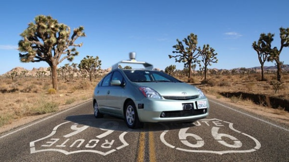 A google driverless car on a stretch of route 66, in the desert. The car is stationary and facing the camera in a posed shot.