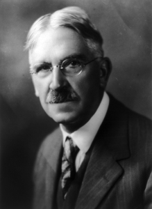 A black and white chest and head portrait of John C. Dewey, an older man with centre-parted white hair, a trimmed mostly dark haired moustache and oval wire-framed glasses.