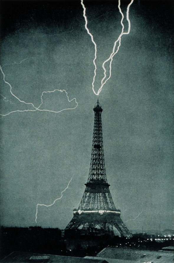 The Eiffel Tower, Paris, at night being struck at the apex by three bolts of lightning simultaneously.