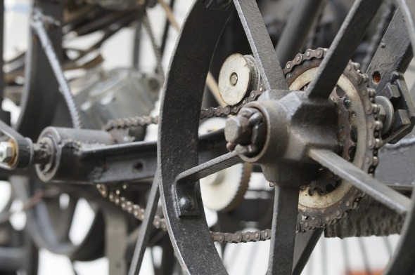 Some cast-iron wheels and gears, connected with a bicycle chain.
